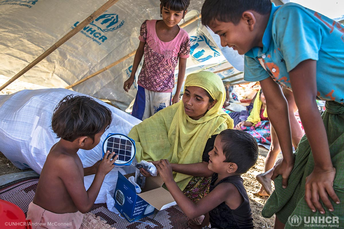 Rohingya mother Laila Begum, 30, and her children (from left) Aysha, 7, Rogida, 12, Kishmot Ara, 5, and Mohammed Riaz, 13, receive their UNHCR Non-Food Items emergency relief pack in their makeshift shelter