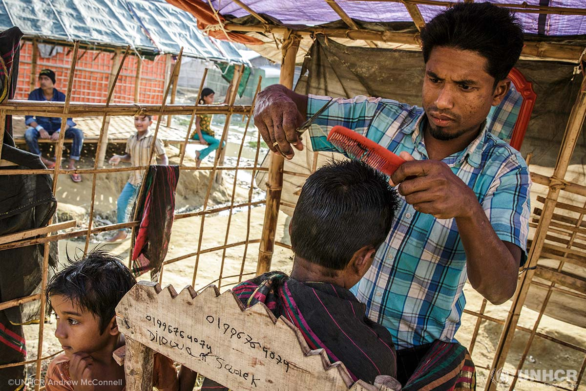 Hairdresser Najibullah, 28, cuts a customer's hair at his barber's shop in Moynerghona refugee camp, Bangladesh. Najibullah was a barber in Myanmar and borrowed some money from a neighbour in the camp to open his shop.