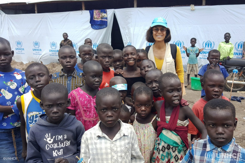 Massoumeh Farman Farmaian stops for a picture with South Sudanese refugee children in Uganda's Rhino camp.