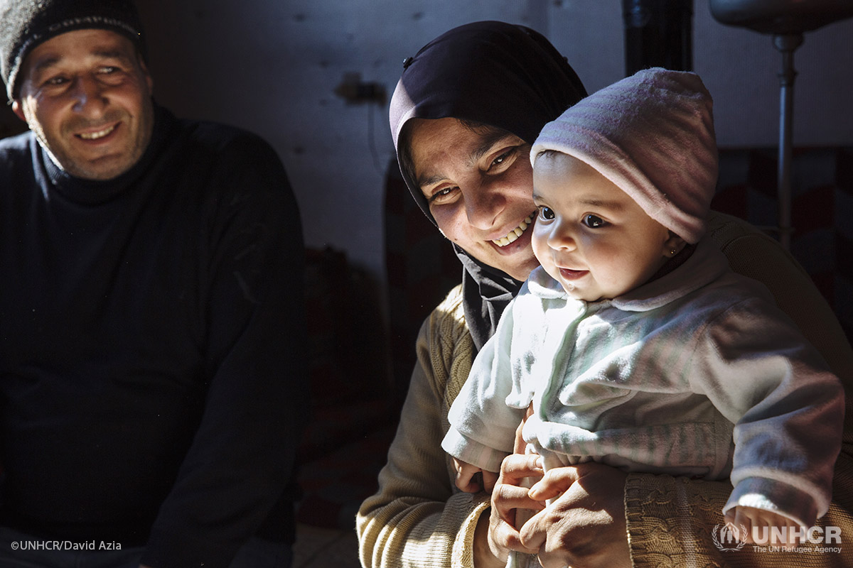 Syrian refugee Samira, 38, holds her six-month-old niece Mona alongside her husband Khaled, 45, a Palestinian refugee displaced from Syria, on the floor of the apartment they share with their family in a substandard building in Barelias, Bekaa Valley, Lebanon.