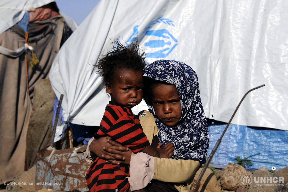 A girl carries her brother outside their tent at the Dharawan settlement.