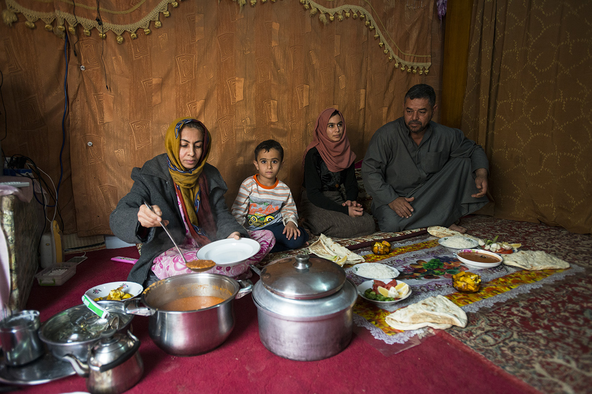 Hamid, Fatma and their children, who were forced to flee violence in Fallujah, Iraq, sit down to a meal.