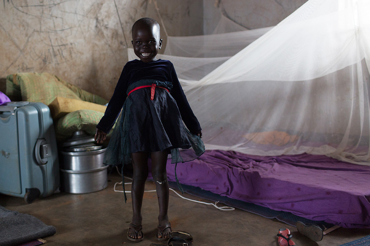 A young refugee from South Sudan stands next to a bed protected with a mosquito net. The insecticide added to the nets kills the mosquitoes before they can transmit the disease.