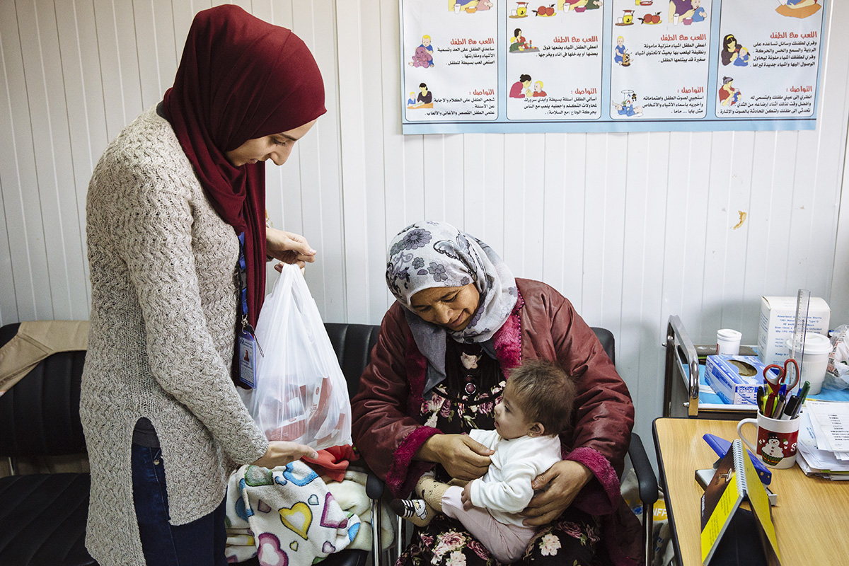Syrian refugee Amani dresses Jena, her 8-month-old daughter, following an appointment with a nutritionist at a UNHCR-funded clinic in Jordan's Azraq refugee camp. Amani is also receiving a supply of ready-to-use food to take home for Jena.