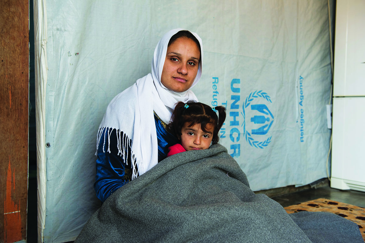 Syrian refugee Amira, with her daughter Amani, keeps warm in their shelter in Lebanon's Bekaa Valley.