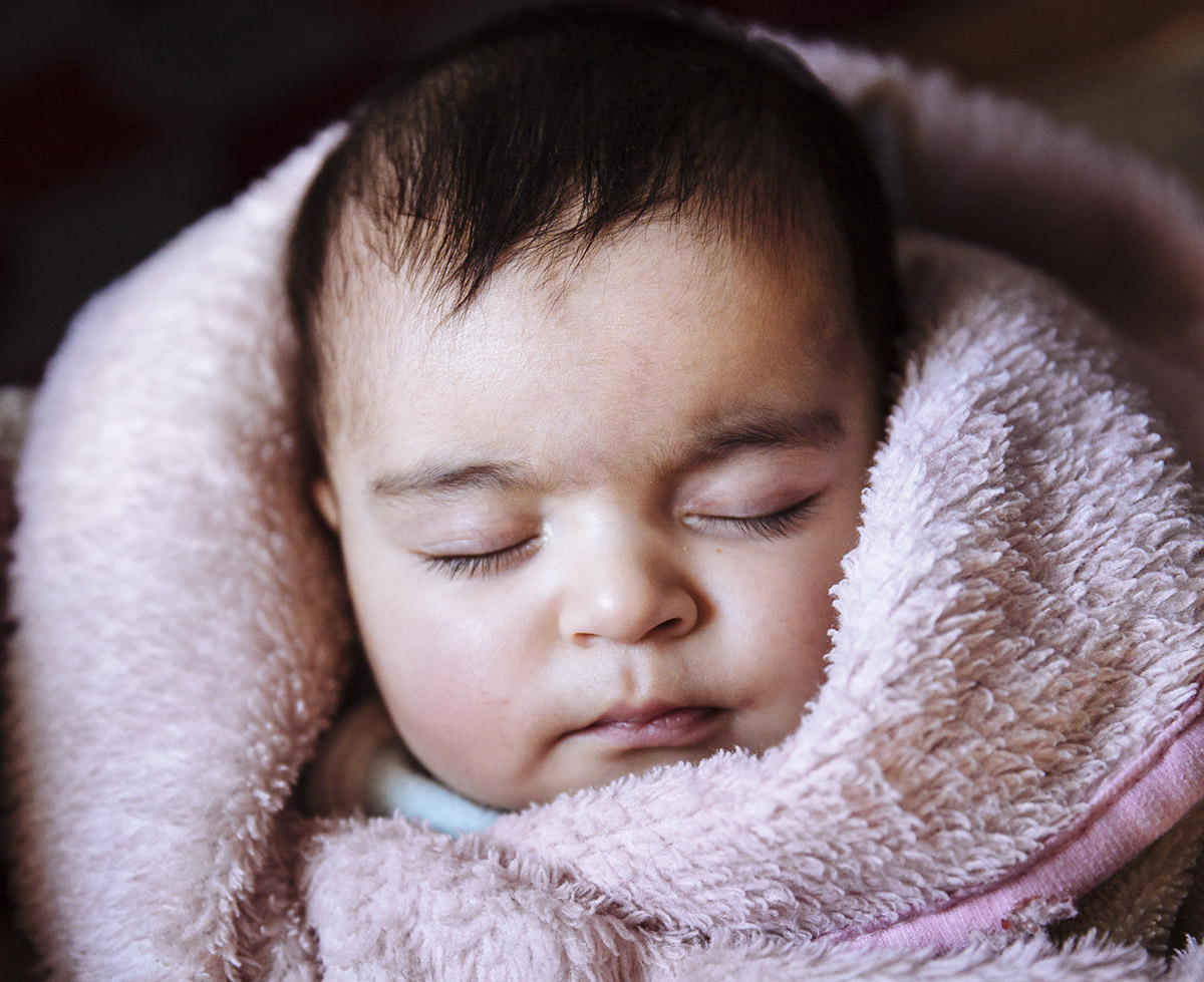 Six-month old Syrian refugee Mona is sleeping in her thermal blanket provided by UNHCR.