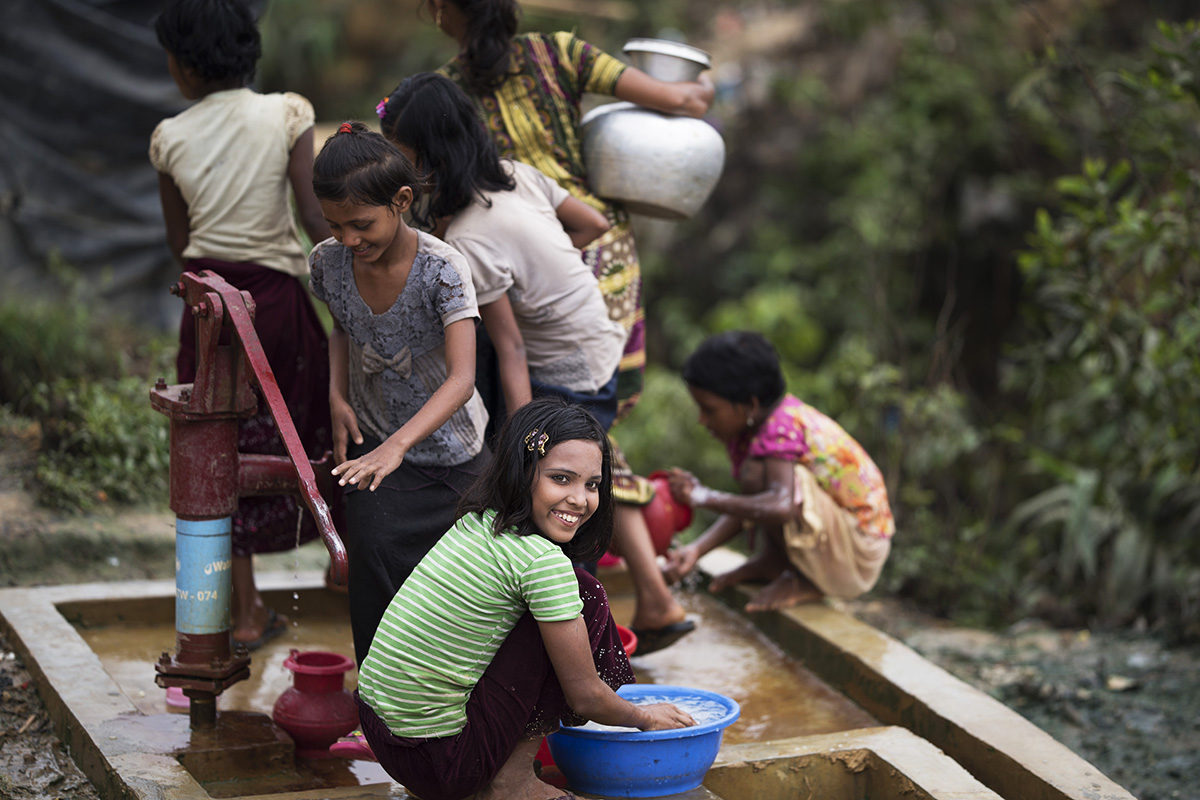 Rohingya girls pump water and wash laundry at a well site in Kutupalong refugee camp, Bangladesh.