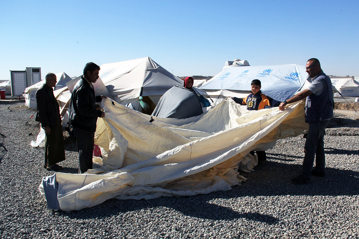 A displaced Iraqi family assembles their tent at Hasansham camp.