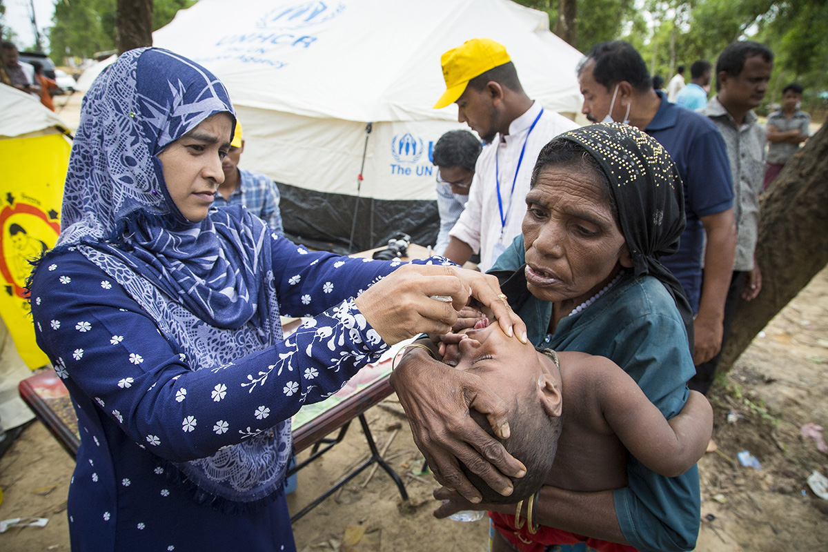 A doctor administers medicine and vaccines to a Rohingya refugee child in Bangladesh.
