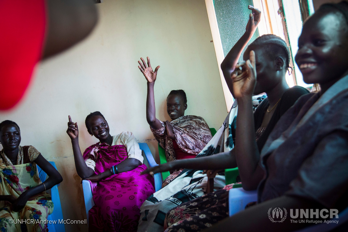 South Sudanese women in a classroom raise their hands