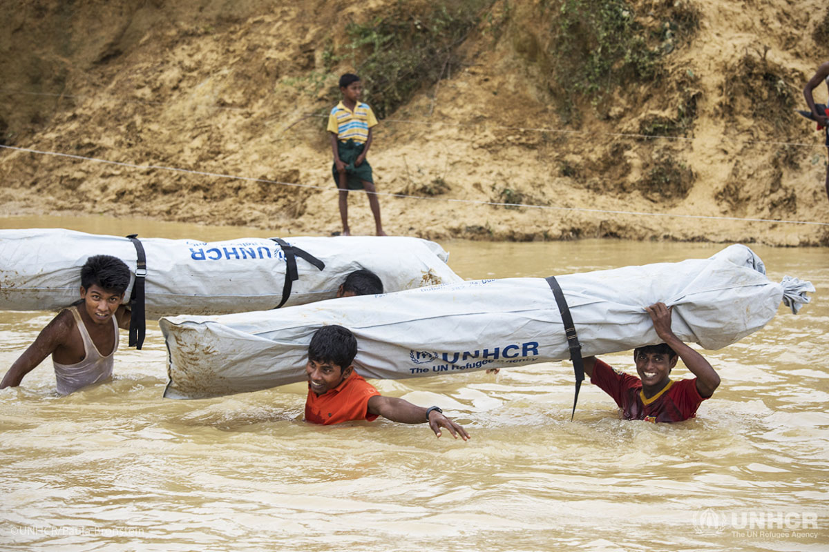 Rohingya refugees carry plastic sheeting through a swelling river.
