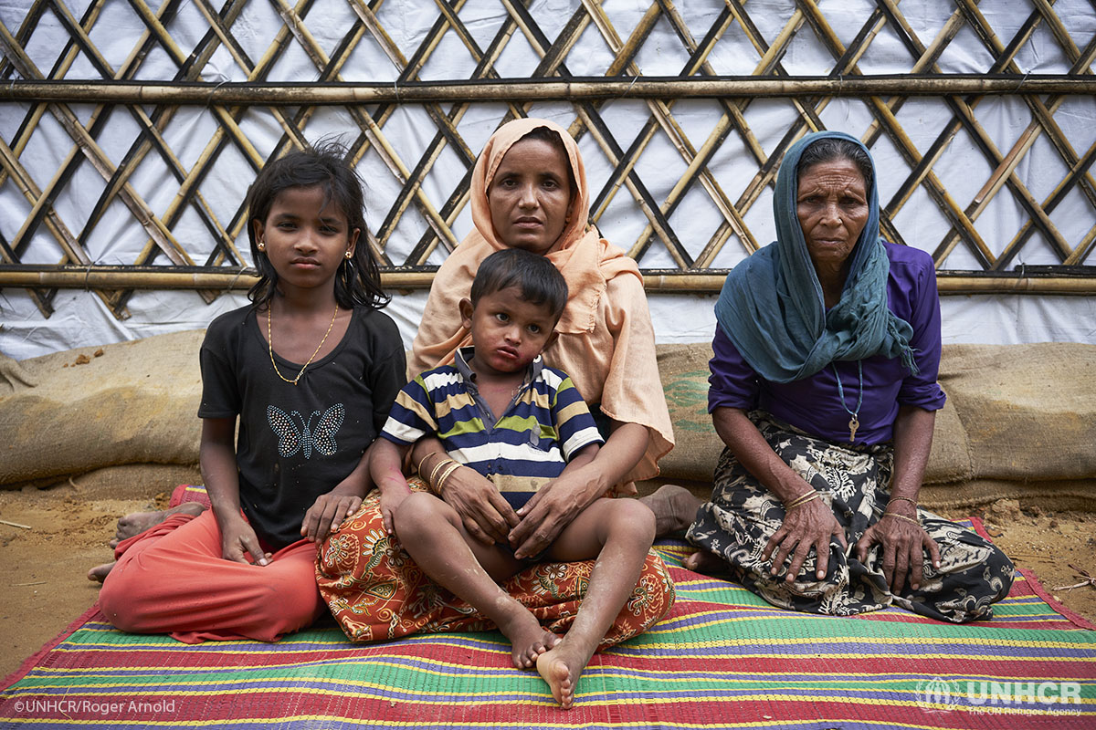 Khadija, her mother and two children sit outside of their new, weatherproofed shelter at Kutupalong refugee camp in Bangladesh.