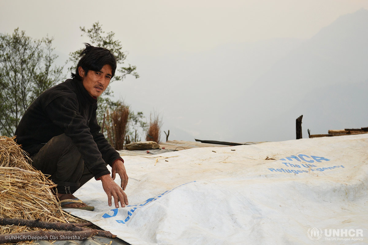 Dhana Lal Tamang, 19, spreads out a reinforced plastic tarp for the roof of his temporary shelter, which the sheeting will protect from heavy rains and wind.