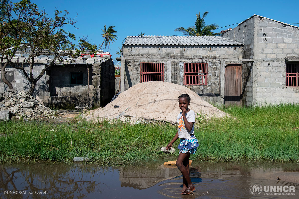 A young girl walks barefoot through floodwater in Beira, Mozambique.