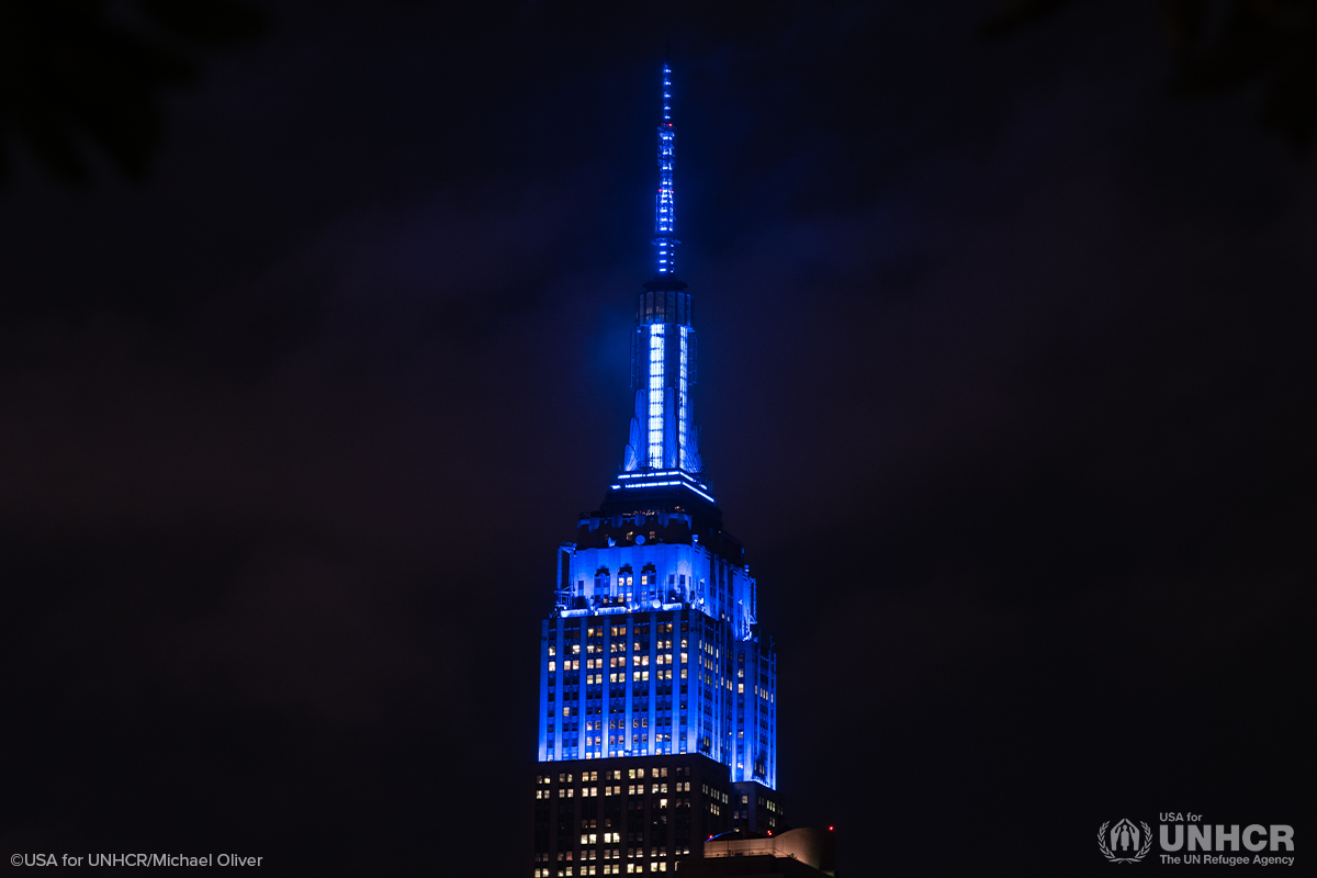 night time shot of empire state building lit up with blue lights