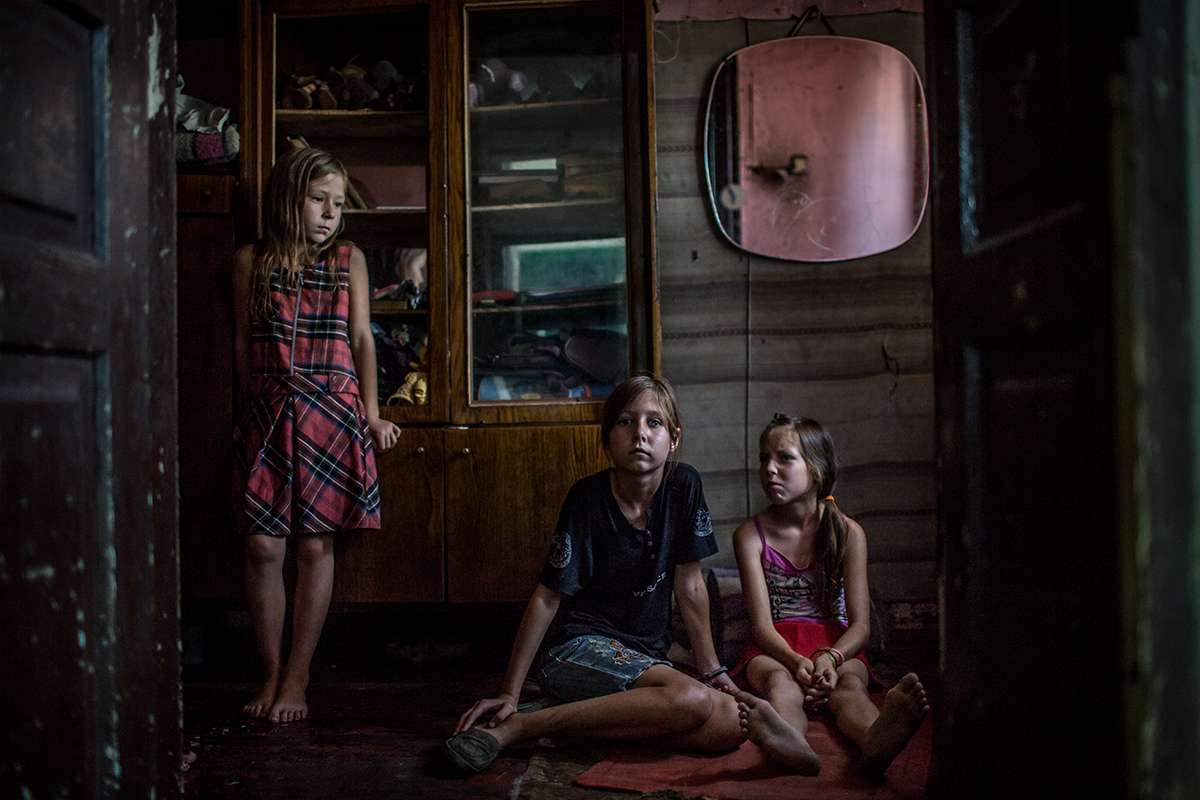 Three young Ukranian sisters sit in their home.