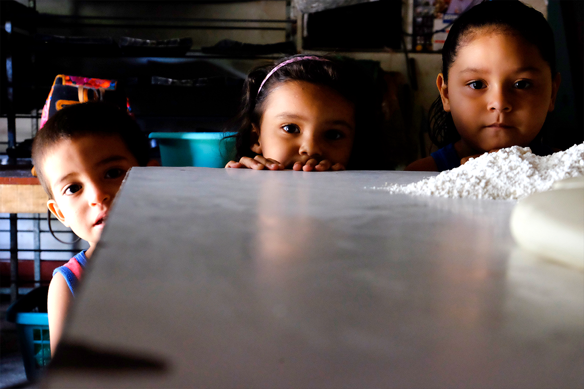 Three Salvadorian children who now live in a bakery in Guatemala after fleeing due to gang violence.