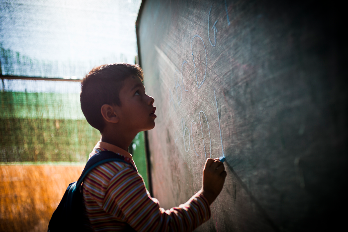 An Afghan boy spells out the alphabet at a refugee camp in Greece.