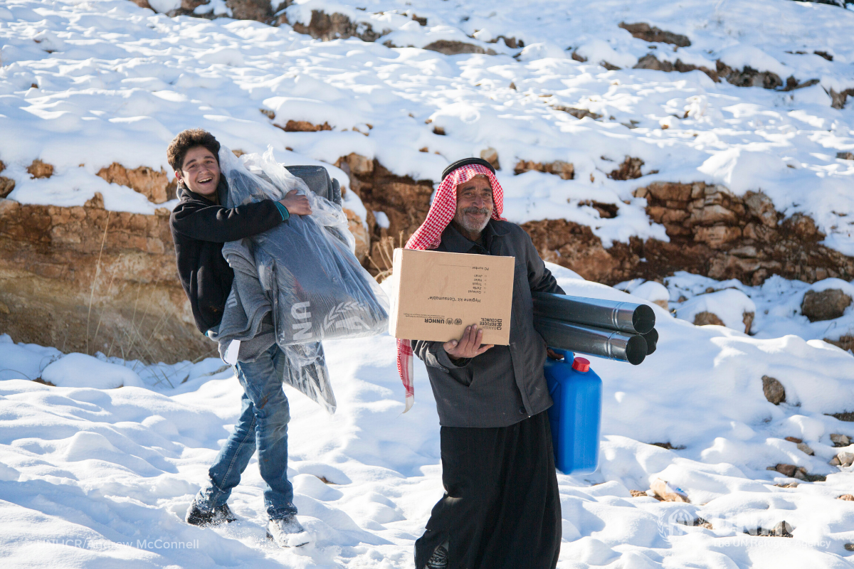 Syrian refugees carrying winter supplies, winter survival kit