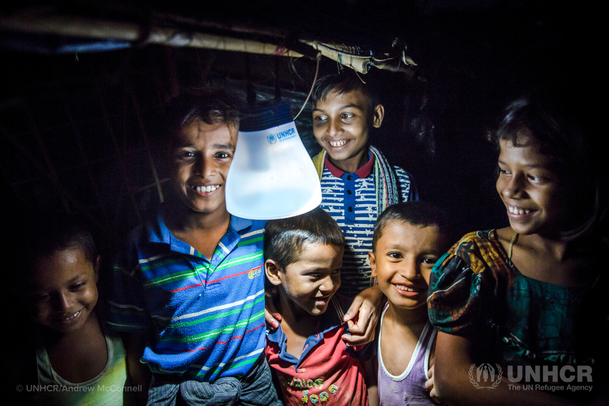 Rohingya children gather around solar lantern