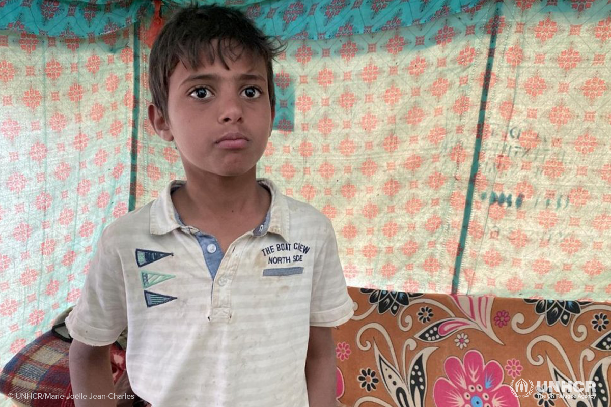 A twelve year old displaced Yemeni boy stands inside the tent he shares with his family