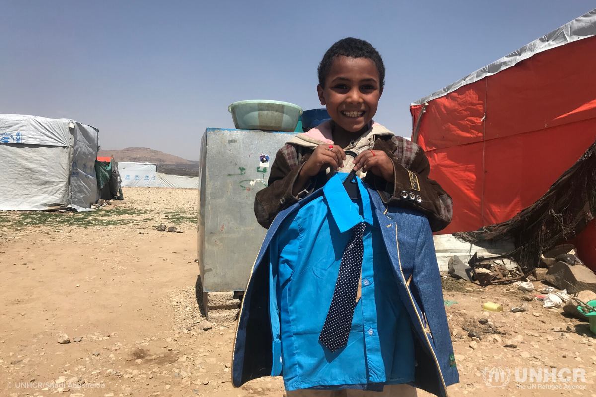 Ghareeb holds his new clothes and smiles