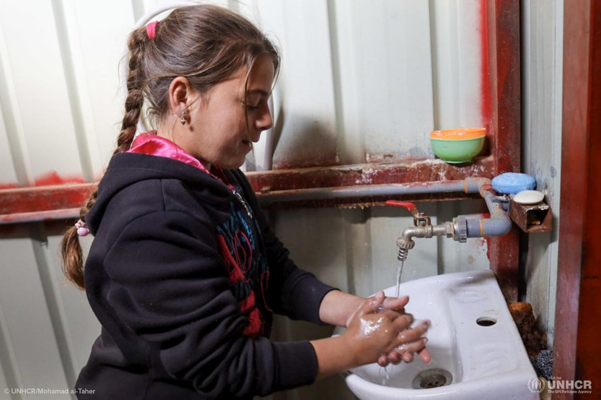 syrian girl washes her hands at za'atari refugee camp
